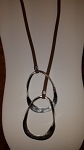 Long brown cord necklace with intertwined silver oval pieces.  Matching earrings