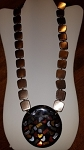 32 inch long brown necklace.  Chain is brown squares with a large round black pendant